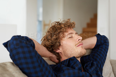 Buy stock photo Shot of a young man relaxing on the sofa at home