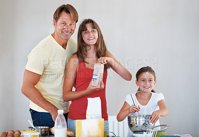 Buy stock photo Portrait of father and daughters having fun in the kitchen while preparing a dessert