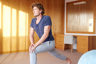 Buy stock photo Shot of a young man exercising in his bedroom