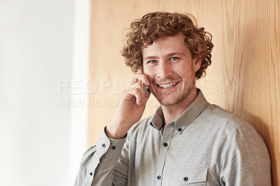 Buy stock photo Cropped portrait of a young businessman talking on his cellphone while working at home