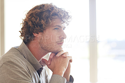 Buy stock photo Cropped shot of a young businessman looking thoughtful while working at home