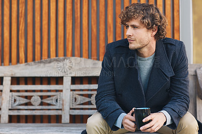Buy stock photo Cropped shot of a young man drinking coffee while sitting on a bench outside
