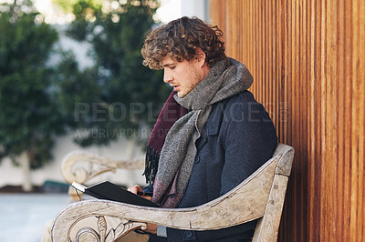 Buy stock photo Cropped shot of a young man reading his diary while sitting on a bench outside