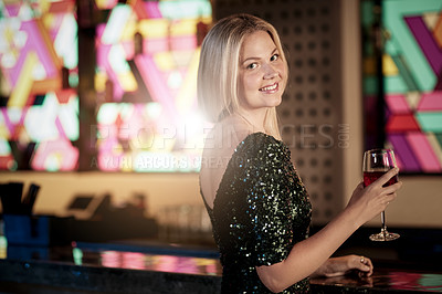 Buy stock photo Shot of a young woman holding a glass of wine while sitting in a bar