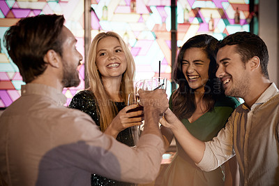 Buy stock photo Shot of a group of friends making a toast in a bar