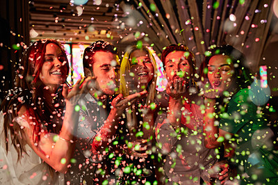 Buy stock photo Shot of a group of friends blowing confetti in a nightclub