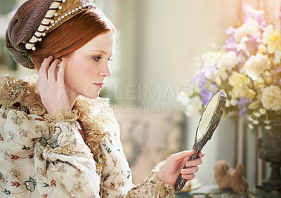 Buy stock photo Shot of an elegant noble woman admiring herself in a mirror in her palace room