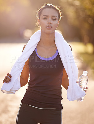 Buy stock photo Shot of a woman holding a towel around her neck after exercising