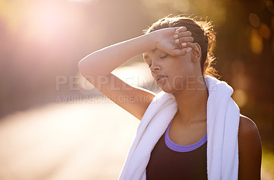 Buy stock photo Shot of a woman wiping away the sweat after some intense outdoor training