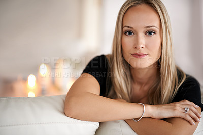 Buy stock photo Portrait of a young blonde woman sitting on her sofa at home