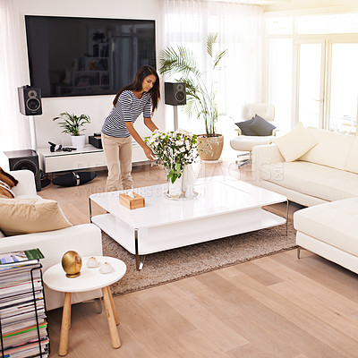 Buy stock photo Shot of a young woman tidying her house