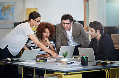 Buy stock photo Shot of designers talking together over laptops in an office