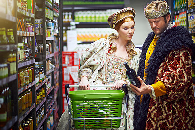 Buy stock photo Shot of a king and queen looking at goods while shopping in a modern grocery store