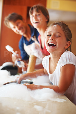 Buy stock photo Portrait of a cute young girl smiling while washing dishes with her mom and dad