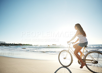 Buy stock photo Full length shot of a young woman cycling on the beach