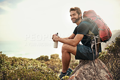 Buy stock photo Shot of a young man taking a water break while out hiking