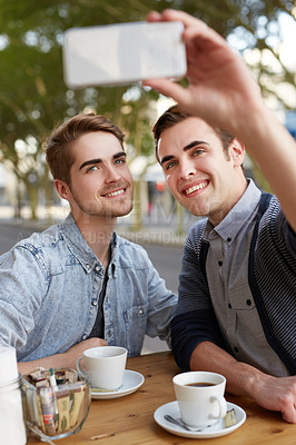 Buy stock photo Shot of a young couple taking a selfie at a cafe
