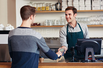 Buy stock photo Shot of a customer paying for a coffee with a credit card