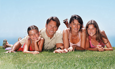 Buy stock photo Family of four lying together on grass and smiling