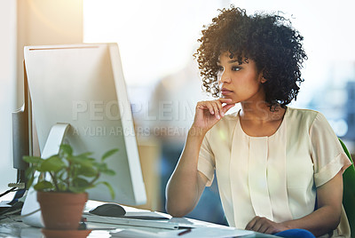 Buy stock photo Shot of a young designer working at her computer in an office