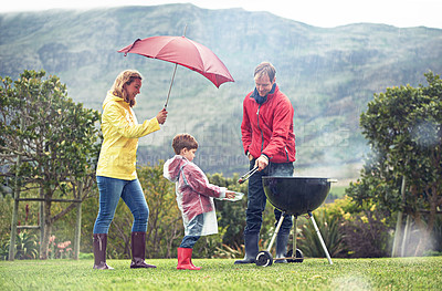 Buy stock photo Shot of a family having a barbecue outside in rainy weather