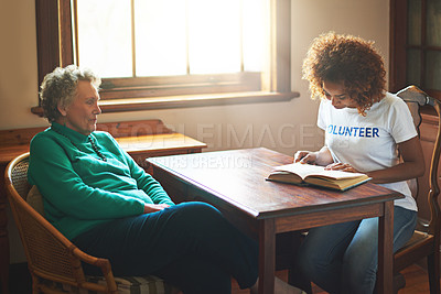 Buy stock photo Shot of a volunteer reading to a senior woman at a retirement home