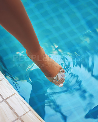 Buy stock photo Cropped shot of a woman dipping her feet in the water of a pool