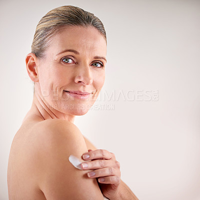 Buy stock photo Cropped studio portrait of a mature woman applying moisturizer to her skin