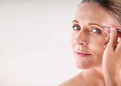 Buy stock photo Cropped portrait of a mature woman plucking her eyebrows with a pair of tweezers