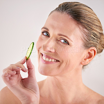Buy stock photo Cropped studio portrait of a mature woman holding up a slice of cucumber