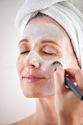 Buy stock photo Cropped shot of a mature woman applying a mask to her face
