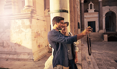 Buy stock photo Shot of a young couple taking a selfie while touring a foreign city