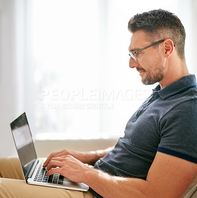 Buy stock photo Shot of a man using his laptop at home