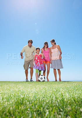 Buy stock photo Full length of family playing football on grass - copyspace