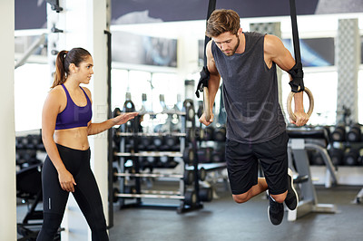 Buy stock photo Shot of a young man going through a workout on the gymnastics rings with his personal trainer