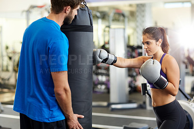 Buy stock photo Cropped shot of a young woman working with her coach on the punching bag