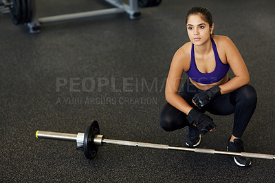 Buy stock photo High angle shot of a young woman crouching beside a barbell in the gym