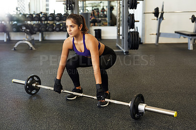 Buy stock photo Full length shot of a young woman lifting a barbell in the gym
