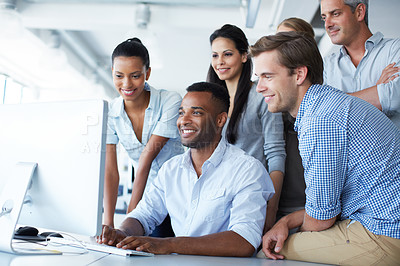 Buy stock photo Shot of a group of colleagues using a computer together in an office