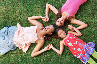 Buy stock photo Top view of mother and her daughters lying on the grass with their heads together