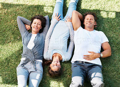 Buy stock photo Top view of man and woman relaxing on grass with their daughter