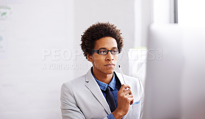 Buy stock photo Shot of a young designer working on a computer in his office