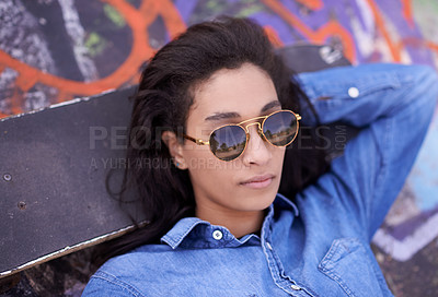 Buy stock photo Shot of a young skateboarder relaxing at a skatepark