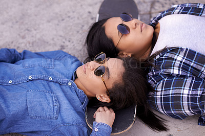 Buy stock photo Shot of two young friends hanging out together at a skatepark