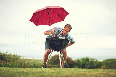 Buy stock photo Shot of a man trying to barbeque in the rain