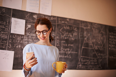Buy stock photo Cropped shot of a young teacher sending a text message while standing in her classroom