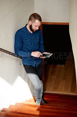 Buy stock photo Full length shot of a young man using his digital tablet while standing on a staircase at home