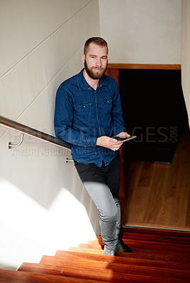 Buy stock photo Full length portrait of a young man using his digital tablet while standing on a staircase at home