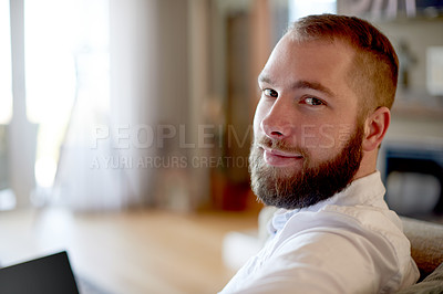 Buy stock photo Portrait of a young man using a laptop on the sofa at home