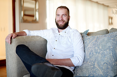 Buy stock photo Portrait of a young man sitting on the sofa at home
